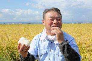 稲田でおにぎりを食べるシニア男性の写真素材 [FYI02054511]