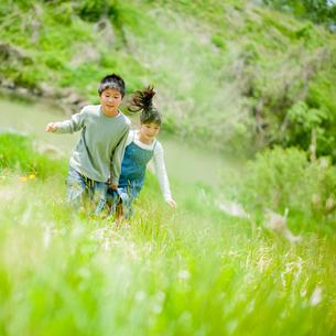 新緑の中を走る男の子と女の子の写真素材 [FYI02054529]