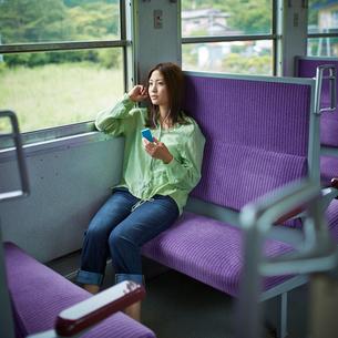 列車の中で音楽を聴く女性の写真素材 [FYI02054532]
