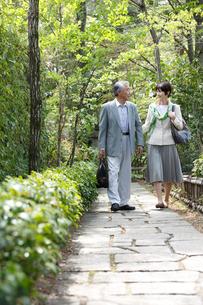 旅行カバンを持って歩くシニア夫婦の写真素材 [FYI02054554]
