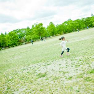 新緑の公園を走る女の子の写真素材 [FYI02054561]