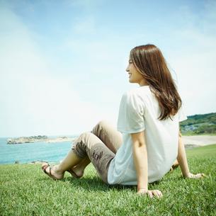 芝生の上に座り海を眺める女性の写真素材 [FYI02054578]