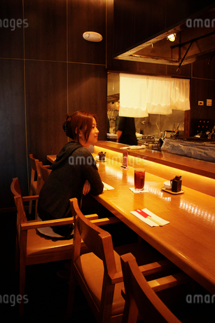 バーカウンターに座る女性の写真素材 [FYI02054598]