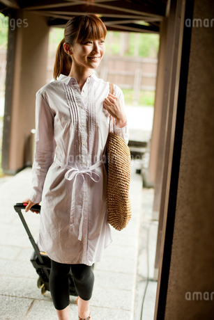 キャリーバッグを引いて歩く女性の写真素材 [FYI02054613]