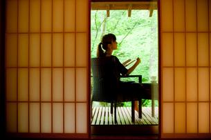 ウッドデッキの椅子に座りくつろぐ女性の写真素材 [FYI02054617]