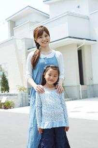 家の前に立つ女の子と母親の写真素材 [FYI02054620]