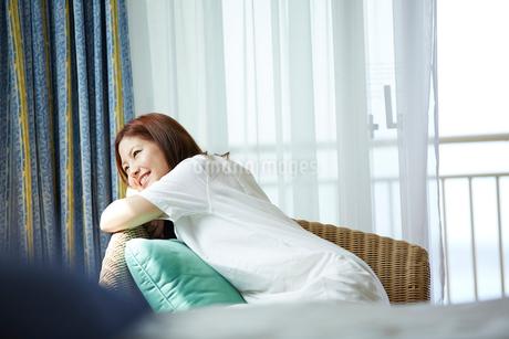 椅子に座りくつろぐ女性の写真素材 [FYI02054626]