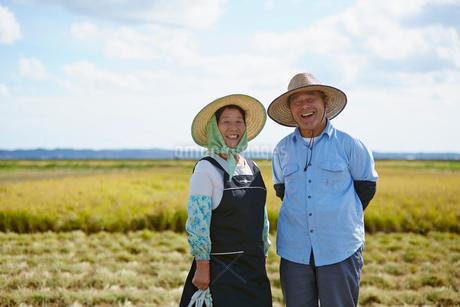 秋の田園に立つ農家の夫婦の写真素材 [FYI02054662]