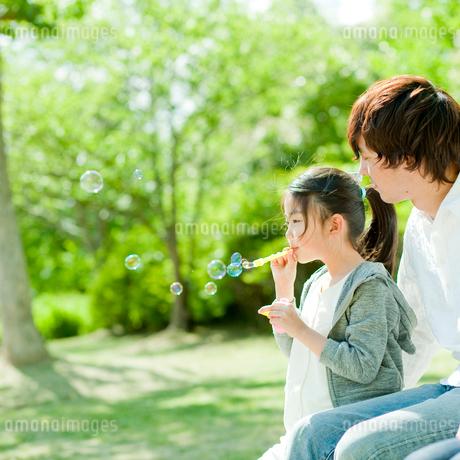 シャボン玉で遊ぶ女の子と父親の写真素材 [FYI02054703]