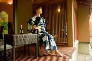 団扇を持ち椅子に座る浴衣姿の女性の写真素材 [FYI02054709]