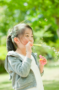 シャボン玉で遊ぶ女の子の写真素材 [FYI02054713]