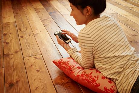 フローリングの床に横たわるスマートフォンを持った女性の写真素材 [FYI02054723]