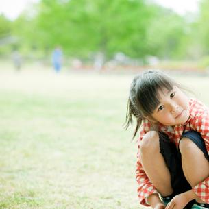 新緑の公園でしゃがむ女の子の写真素材 [FYI02054731]