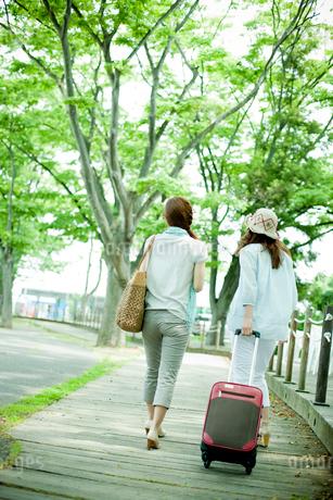 旅行カバンを持った2人の女性の後ろ姿の写真素材 [FYI02054743]