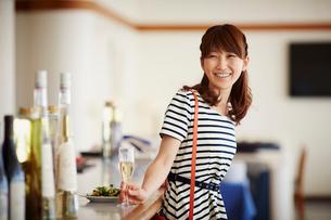 レストランのカウンターでシャンパンを持つ女性の写真素材 [FYI02054772]