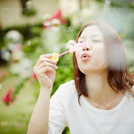 シャボン玉を吹く女性の写真素材 [FYI02054775]