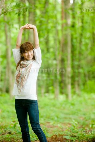 新緑と伸びをする女性の写真素材 [FYI02054822]
