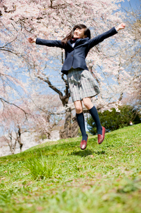ジャンプする女子中学生と桜の写真素材 [FYI02054826]