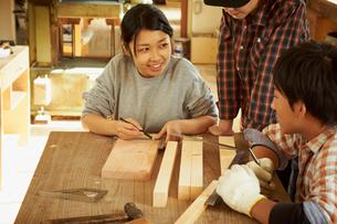 木材に印を付ける3人の若者達の写真素材 [FYI02054856]