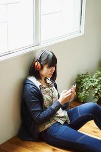 スマートフォンで音楽を聴く10代女性の写真素材 [FYI02054899]