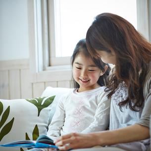 ソファに座る笑顔の女の子と母親の写真素材 [FYI02054914]