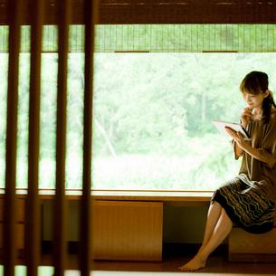 窓辺でタブレットPCを見る女性の写真素材 [FYI02054922]