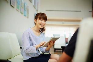 タブレットPCを持ち商談をする女性の写真素材 [FYI02054935]