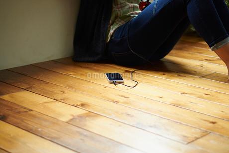 床に座る女性とスマートフォンの写真素材 [FYI02054954]