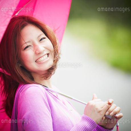 傘をさす笑顔の女性の写真素材 [FYI02054955]