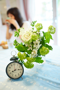 目覚まし時計と花と女性の写真素材 [FYI02054961]