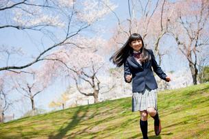 桜咲く公園を走る女子中学生の写真素材 [FYI02054994]