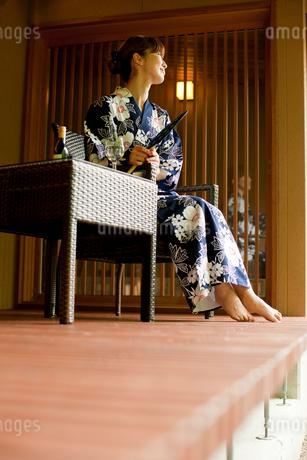 団扇を持ち椅子に座る浴衣姿の女性の写真素材 [FYI02054995]