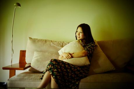 クッションを抱いてソファに座る女性の写真素材 [FYI02055009]