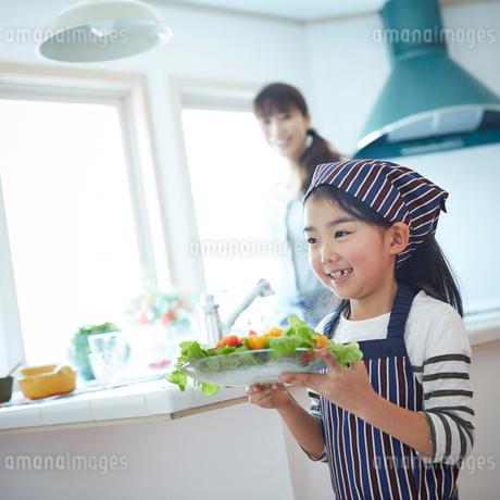 サラダを運ぶエプロン姿の女の子の写真素材 [FYI02055014]