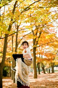 母親に肩車される笑顔の女の子と紅葉の木々の写真素材 [FYI02055054]