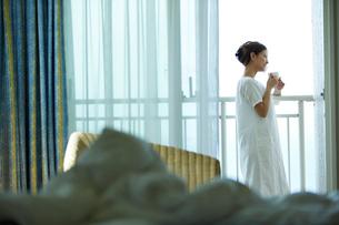 コーヒーカップを持ちベランダから外を眺める女性の写真素材 [FYI02055084]
