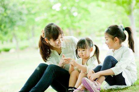 新緑の公園に座る2人の女の子と母親の写真素材 [FYI02055151]