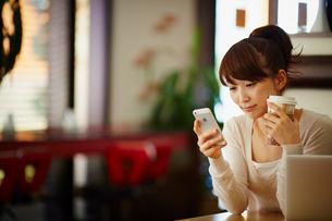 カフェでコーヒーを飲みながらスマートフォンを見る女性の写真素材 [FYI02055225]