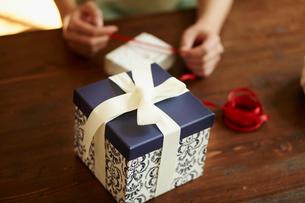 ギフトボックスにリボンを結ぶ女性の手元の写真素材 [FYI02055237]