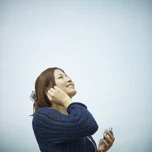 音楽を聴く女性と青空の写真素材 [FYI02055254]