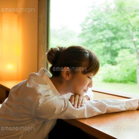 窓辺でうたた寝をする女性の写真素材 [FYI02055315]