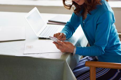 ノートパソコンやスマートフォンで仕事をする女性の写真素材 [FYI02055340]