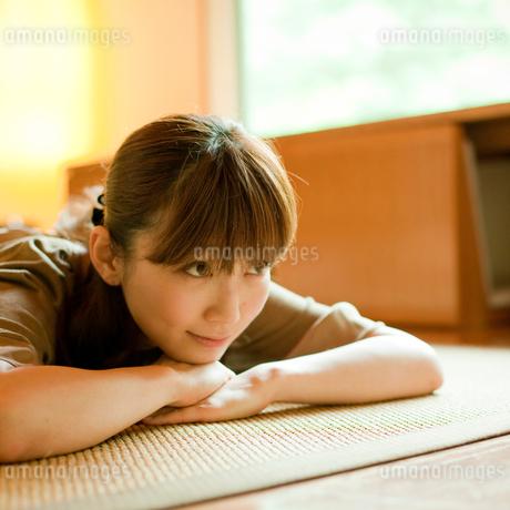 床に寝転ぶ女性の写真素材 [FYI02055365]