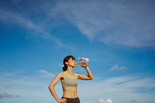 水を飲むスポーツウェア姿の女性と青空の写真素材 [FYI02055386]