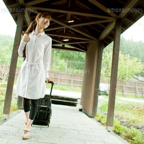 キャリーバッグを引いて歩く女性の写真素材 [FYI02055482]