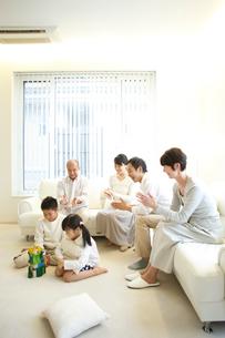 積木で遊ぶ子供達とソファに座り拍手をする両親と祖父母の写真素材 [FYI02055490]