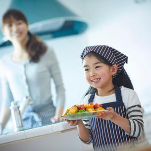 サラダを運ぶエプロン姿の女の子の写真素材 [FYI02055504]
