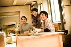 作業台で作業をする3人の若者達の写真素材 [FYI02055538]