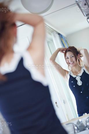 鏡に向かい髪を結う女性の写真素材 [FYI02055587]