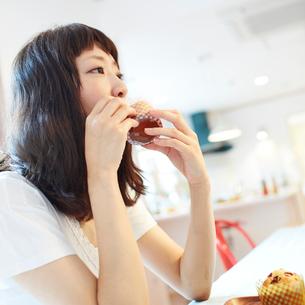 マフィンを食べる若い女性の写真素材 [FYI02055608]